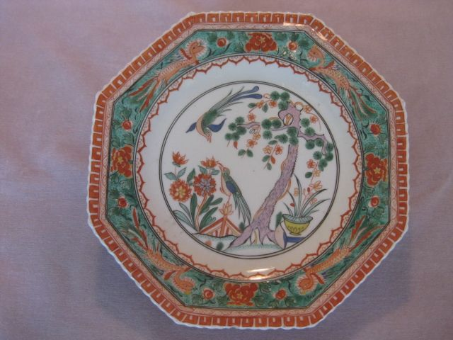 "A rare Woprcester plate painted in the ""famille verte"" style with a pine tree and birds in a garden  and with phoenix birds and flowers and a cell border Unamrked   Circa 1775  Width 9 1/2"""