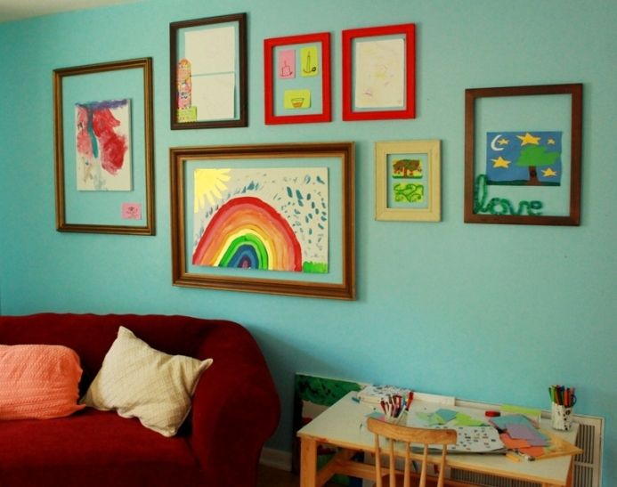 frames are hung and she uses putty to stick pictures directly to wall.  Looks cute, although hard to match frame size and orientation to what the kids are making? can't really switch it up.  I do like that you could put up 3D art and things other than their drawings.