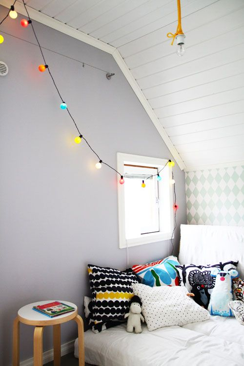A room with colorful cushions and lamps that will make both girls and boys happy.