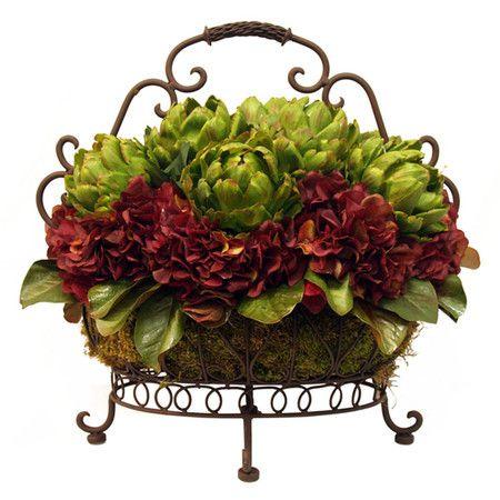 Silk artichoke and hydrangea arrangement in a scrolling footed basket. Product: Faux floral arrangement Constructi...