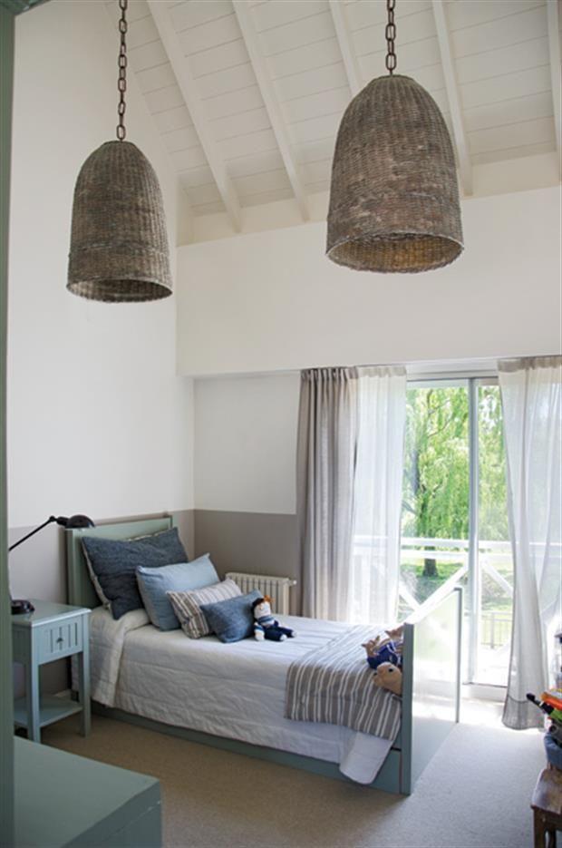 Dormitorio para varón, pintado hasta media altura. Pantallas de mimbre, almohadones azules de seda rústica y cubrecama de lino (todo de Grace Devecyan).. Foto: Living / Mauro Ramírez