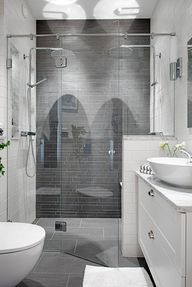 Bath - Grey tiles in an extraordinary two-person shower, the star of this room, is complemented by the Carrera marble countertop & white vessel sink. This space proves that a bath doesn't need to be huge to make a statement..