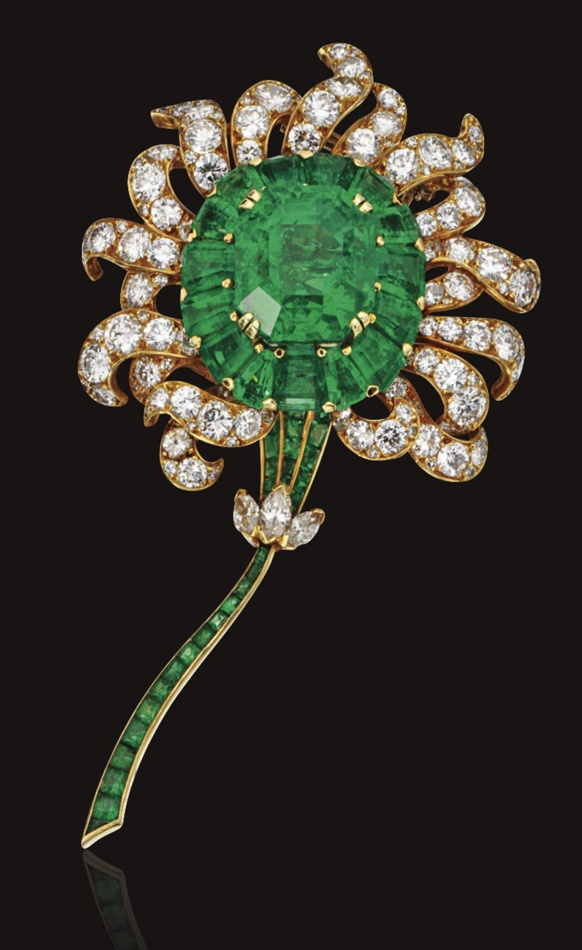 EMERALD AND DIAMOND FLOWER BROOCH, VAN CLEEF & ARPELS, NEW YORK.  The stylized flower set in the center with an emerald-cut emerald weighing 21.61 carats, framed by 15 tapered rectangular-shaped emeralds, the petals set with 54 round diamonds, the stem of calibré-cut emeralds accented with 3 marquise-shaped diamonds, the total diamond weight approximately 9.75 carats, mounted in 18 karat gold, signed Van Cleef & Arpels, numbered N.Y. 27588.