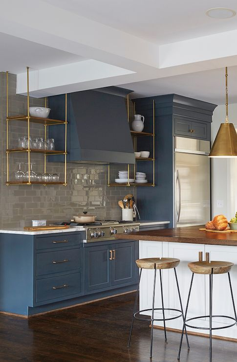 Stunning kitchen features blue cabinets adorned with brass hardware paired with white marble countertops and a gray subway tiled backsplash.