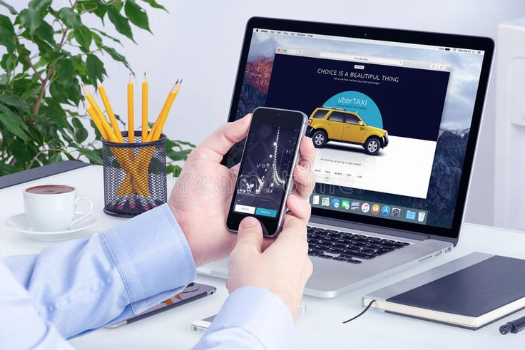 Uber app on iPhone in man hands and Uber website on