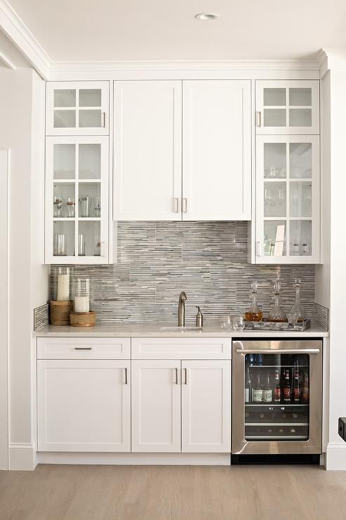 White and gray dining room wet bar boasts a stainless steel glass front beverage fridge placed beside white shaker cabinets located beneath a marble countertop fitted with a small sink and a satin nickel faucet placed in front of gray mosaic backsplash tiles partially framing glass front upper cabinets.