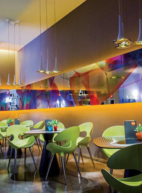 Mesas con sillas Kat color lima diseñadas por Karim Rashid para Redi y paredes color naranja en el hotel italiano Nhow Milano.