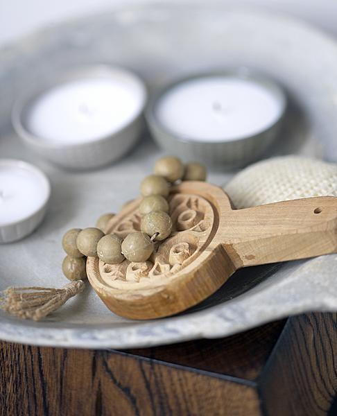 Een mooi object voor in de badkamer kun je gemakkelijk zelf maken met voorwerpen zoals een zeepketting, een scrubspons en kaarsjes.