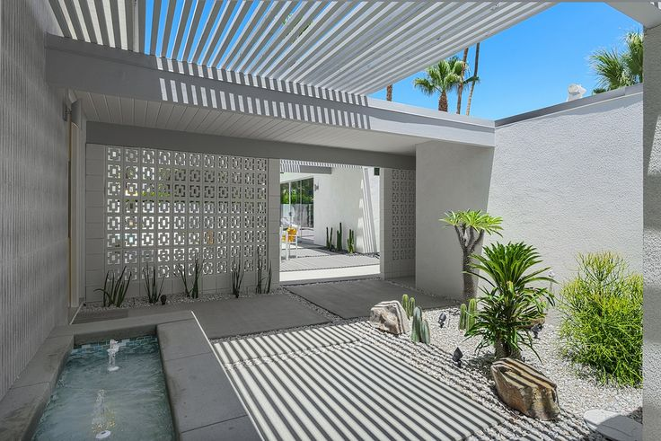 Daytime view through mid century decorative block privacy wall, entry fountain - Laverne project by H3K Design