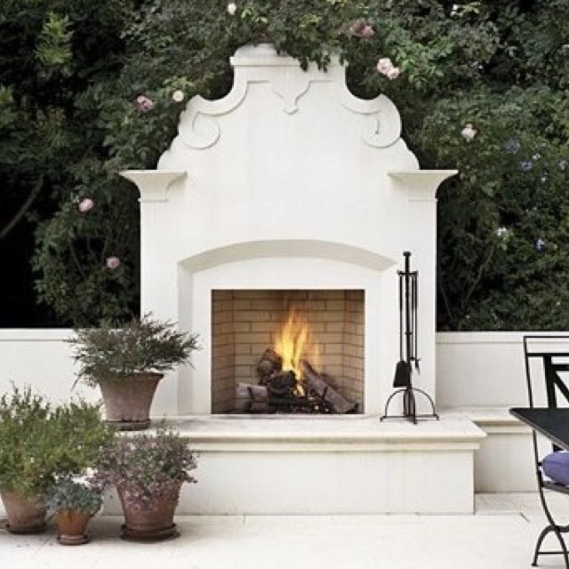 Love this outdoor fireplace.  So pretty and classic.