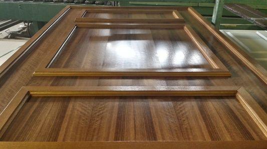 Pannello per porta blindata costruito artigianalmente con elementi applicati in noce figurato