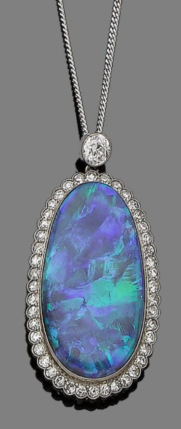 An opal and diamond pendant necklace, circa 1915 The oval cabochon opal,  within a surround of single-cut diamonds, suspended from a brilliant-cut  diamond, ...