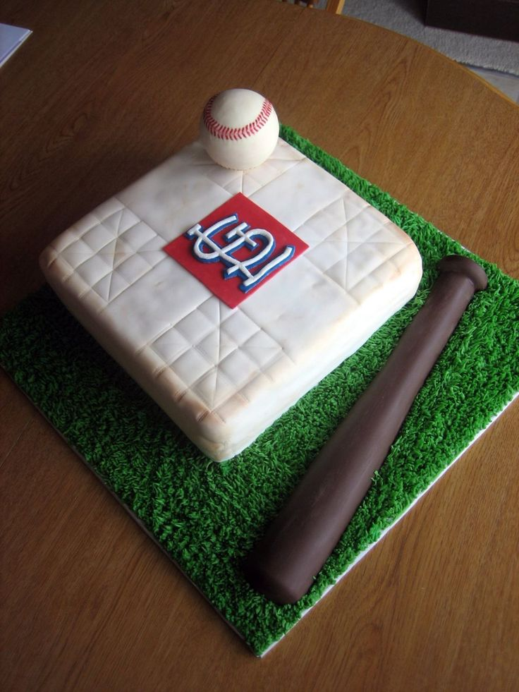Clark's first birthday cake - The base is yellow cake covered with white fondant, and was then dusted with cappuccino and mushroom colored petal dusts to resemble dirt. The baseball is solid white chocolate and the baseball bat is solid dark and white chocolate combined. The grass was created using butter cream icing.