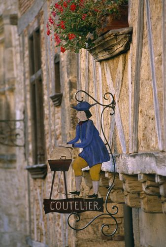 A sign and flowers in the historic village of Saint Cirq Lapopie, Dordogne, France