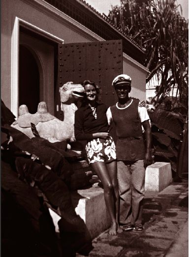 Doris Duke with surfer and musician Sam Kahanamoku at the entrance to Shangri La, circa 1939.
