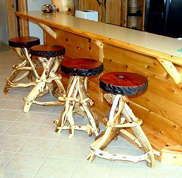 The artisans of Woodland Creek furniture handcrafted these artistic log bar stools. Each is made from solid, natural juniper logs. Juniper has an incredible grain pattern, character, and natural color. Each branch is fitted and sanded by hand. The seat is a solid piece of redwood contrasting the lighter colors of the logs. These stools