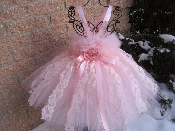 Blush pink lace, pale pink tutu dress, baptism gown, christening dress, birthday tutu dress, flower girl gown, girls tutu dress, photo shoots, princess tutu dress, party tutu dress. Available in baby and toddler sizes. This stunning tutu dress is a very soft pale, baby pink. It has a top layer of beautiful pale blush colour lace strips. The bodice of the dress has a bit of fluff.  The TOTAL LENGTH OF THE DRESS IS MEASURED FROM UNDER THE ARMPIT TO WHERE YOU WANT THE DRESS TO FALL. Please…