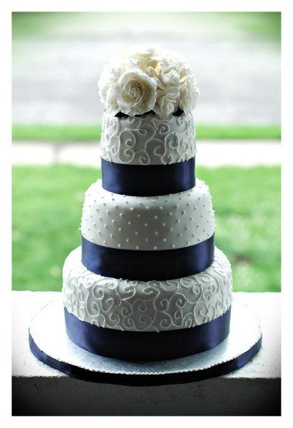 Lace, flowers and blue ribbon wedding cake. A little too busy for me - perhaps no flowers on top, no pattern on middle tier.