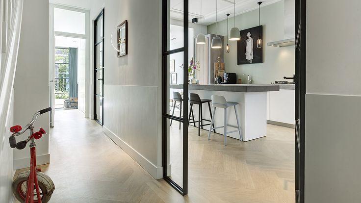 Een moderne lichte stadswoning in Watergraafsmeer met een op maat gemaakte keuken als het hart van de woning. De houten visgraatvloer verbindt de ruimten en brengt warmte in de woning. De stalen deuren zorgen voor een industrieel modern karakter. Het ontwerp is van de hand van BNLA architecten in Amsterdam. Fotografie: Wim Hanenberg.
