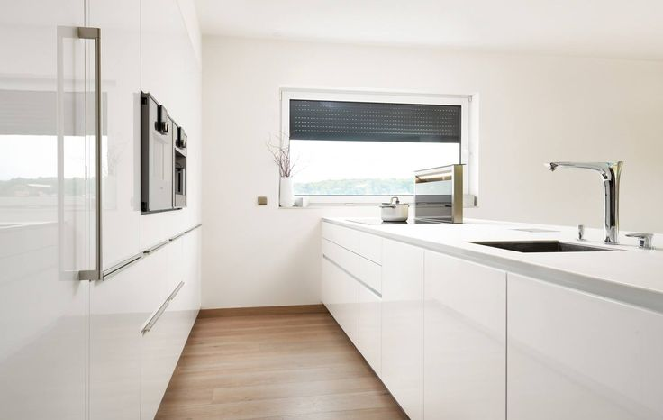Modern white kitchen with clean lines and sleek appliances by Hans Krug