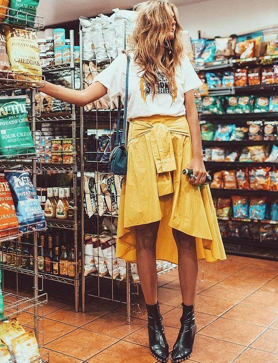 Como usar amarelo em diversos looks: guia completo. T-shirt branca com estampa, saia midi assimétrica, ankel boot, botinha preta com vernis