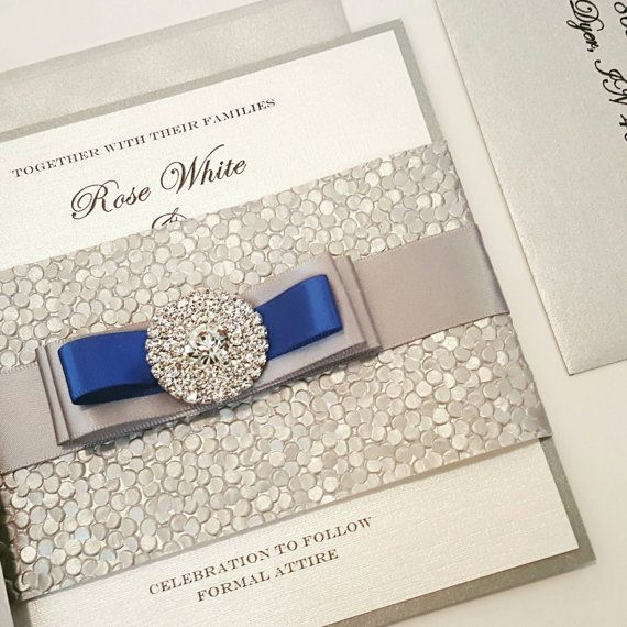 This is part of our New Stunning Pebbles Collection .Features a gorgeous Silver Pebbles band with a triple layer bow and a lovely crystal jewel.  Check out our 100% positive reviews!   Pricing:  1 to 99= $6.00 100 or more= $5.75 200 or more = $5.50  *Matching Table number available @ $4.00 ea The Price of the Suite includes:  * 111 pound Cover Stock (best quality for Cover Paper) * Pebbles Belly Band * Jewel * Ribbon * The wording is printed in a high quality shimmery linen pap...