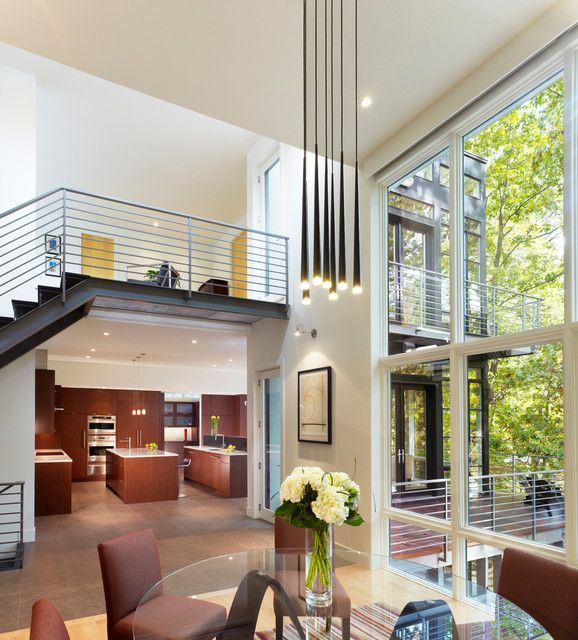 Spacious Double Height Home Living Space Designed With Low Modern Chandeliers Above Round Glass Table