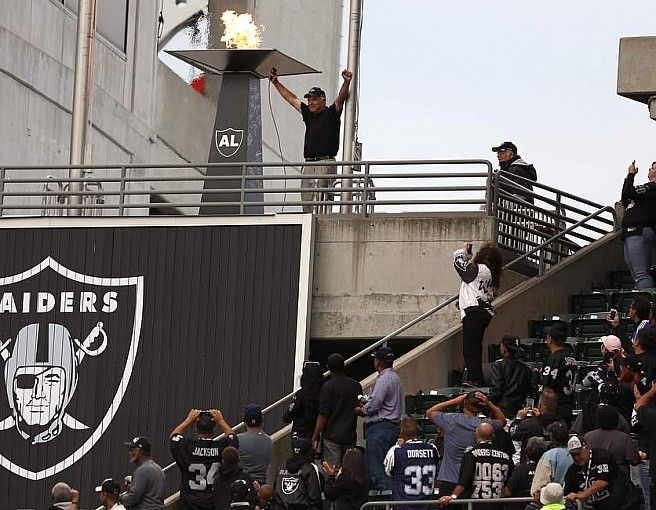 Daryle Lamonica lights the flame before the preseason game between the Oakland Raiders and Dallas Cowboys in Oakland on Friday, August 9, 2013.