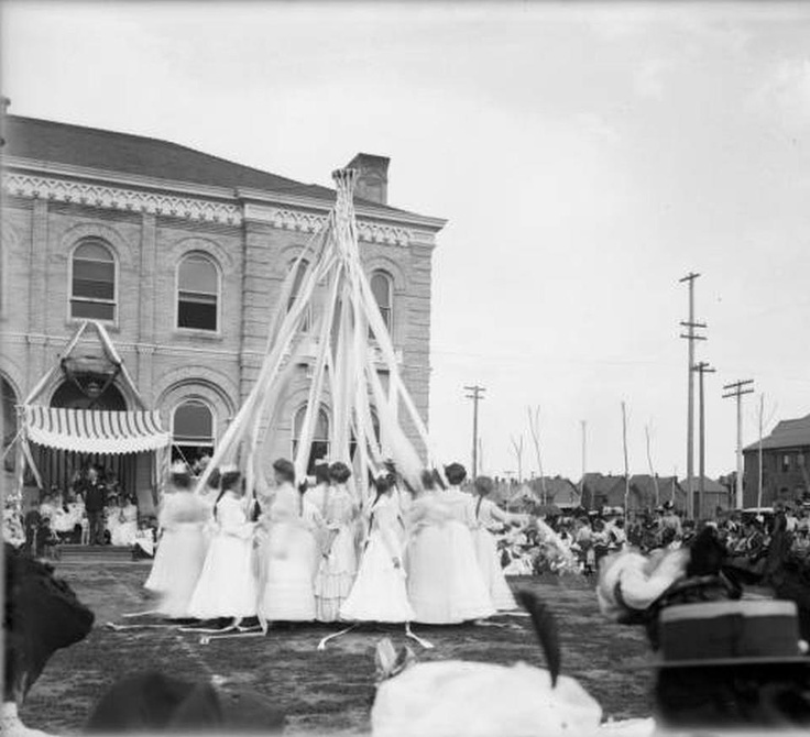 Young ladies from Miss Wolcott's School at 1400 Marion St. dancing around a May Pole in 1910