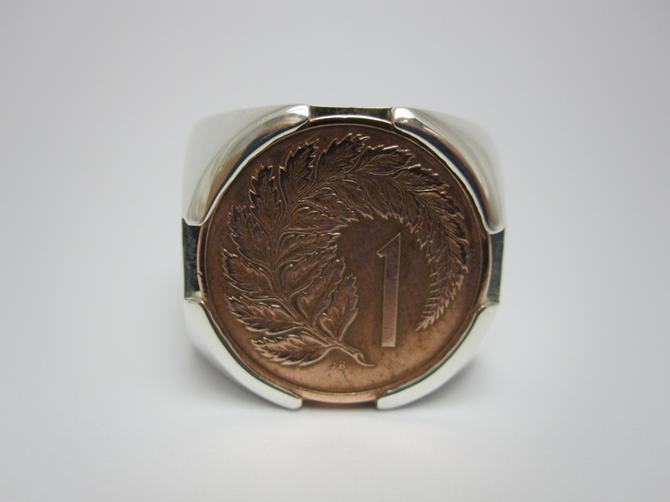 big silver ring holding an old 1cent piece.