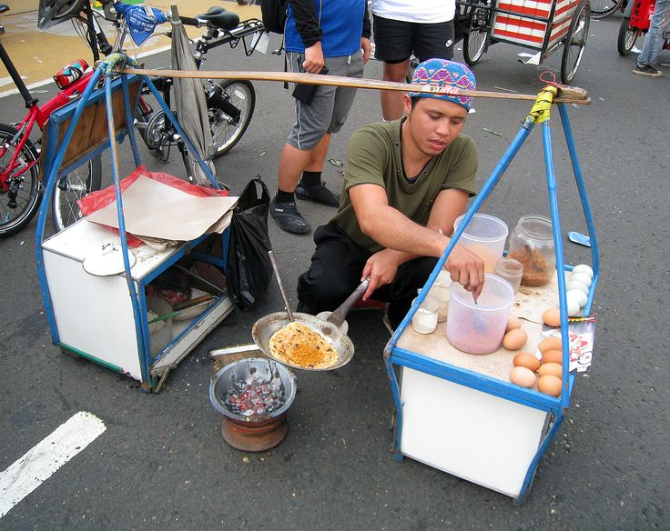Kerak Telor vendor on Jakarta street. Kerak Telor is traditional Betawi spicy omelette dish. Made from the mixture of rice, egg, spices, spicy coconut granule, and fried shallots.