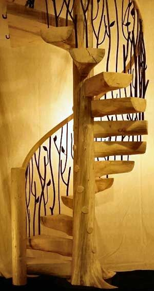 Tree-trunk spiral staircase with iron twig/leaf balustrade...