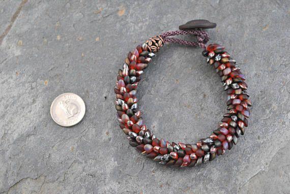 Autumn Dragon Scales Kumihimo Artisan Bracelet #bracelet #kumihimo #kumihimobracelet #artisan #artisanbracelet #handmade #woven #handwoven #handknotted #dragon #dragonscales #magatama #oneofakind #lightweight #flexible #iridescent #rich #warm #red #garnet #burgundy #gunmetal #leather #leatherbutton #beadedbracelet #boho #bohemian #unique #japanese #japaneseweaving