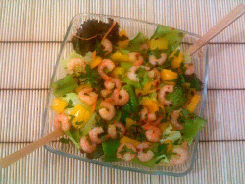 Salada de Camarão e Verdes: 100g. de camarões limpos (frescos ou congelados) 2 colheres de sopa de saquê culinário 3 colheres de sopa de água 1/2 colher de chá de pimenta dedo de moça picadinha ou de pimenta calabresa desidratada +/- 2 colheres de sopa de pimentão 4 ou 5 vagens de ervilha torta 1 colher de sopa de azeite 1 colher de sopa de cebolinha Sal e pimenta do reino a vontade Folhas verdes (alface lisa ou crespa, rúcula, agrião etc.) Cenoura ralada Salsinha picada (opcional)