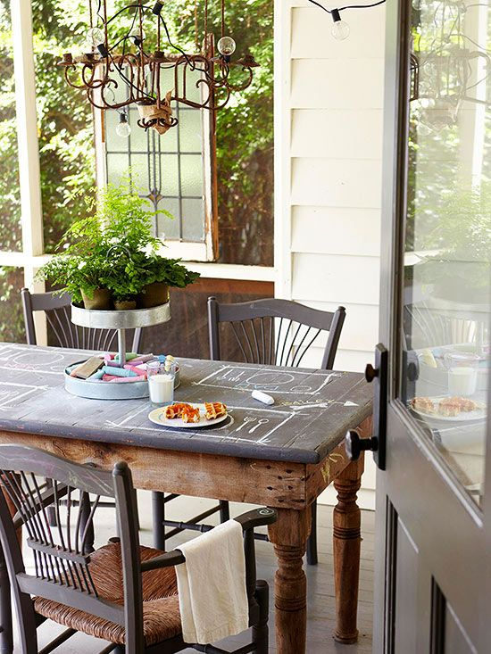 Porch/Patio-A table topped with chalk paint gives kids a fun drawing surface while corbeled table legs bring a certain elegance to the mix. A color palette of charcoal gray, white, and brown keep this patio feeling sophisticated. A wiry chandelier gives the space a slightly vintage feel.