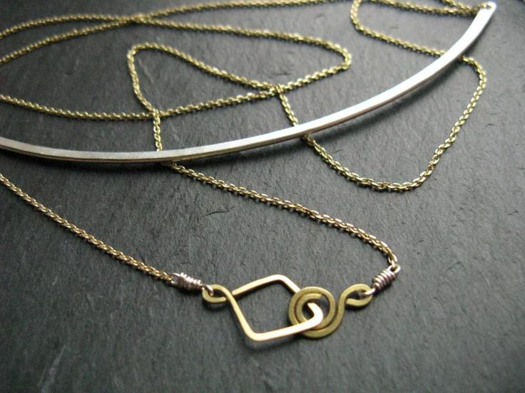 Silver Moon crescent - geometric mixed metal necklace with a wide silver pectoral suspended on a thin delicate golden brass chain. Tribal-inspired minimal statement necklace hand-crafted in gold brass and silver. Contrasting combination of metals for a contemporary look, It has a hand-made lozenge-shaped hook and spiral clasp accentuated by being wrapped with 925 silver wire.  You have the option of wearing the necklace short, with the chain doubled. Open the clasp and pull outwards the…