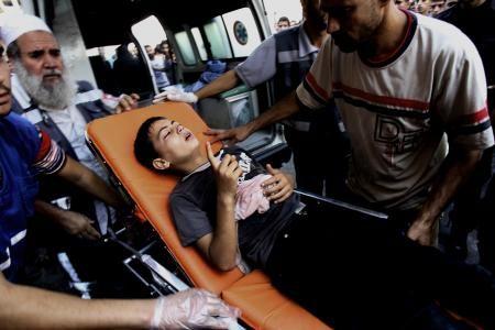 24日、イスラエル軍による国連系学校砲撃で負傷し、搬送される少年=パレスチナ自治区ガザ(AP=共同)