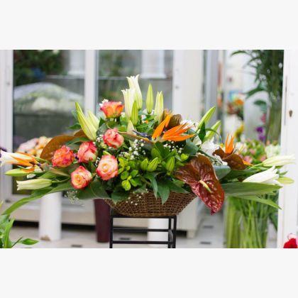 Μεγάλη σύνθεση λουλουδιών σε σχήμα γόνδολας με στερλίτσιες (πουλιά του παραδείσου), τριαντάφυλλα, ανθούρια και λίλιουμ.