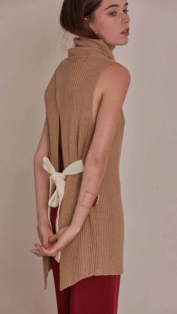 Sofia Sweater, a knit sweater in brown sugar. Turtleneck long sleeve sweater in wool cashmere blend. Vertical ribbing detail, sleeveless and open back with self-tied. Designed to be loose fit. COMPOSI