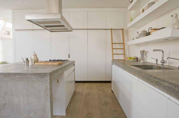 Keuken 6, Paul van de Kooi. Mooie witte keuken beetje landelijk maar wel strak. Door houten vloer toch warme uistraling. Stoer door betonnen blad. Sober door dichte kastenwand, plafondhoog, dus veel bergruimte. Zo'n laddertje er bij is een leuke oplossing