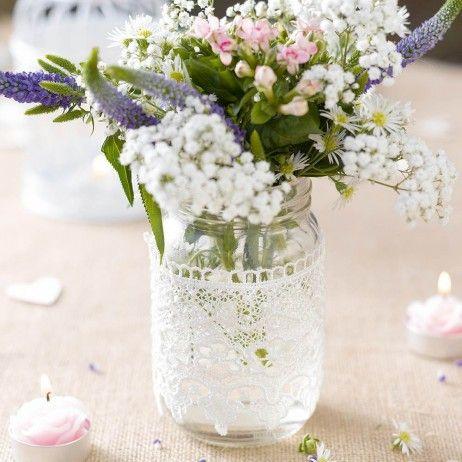 Ce bocal en verre façon Mason Jar enveloppé de dentelle blanche est un élément idéal pour une décoration de table de mariage rustique ou champêtre.