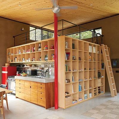 Clutter-control cubbies    With storage and display shelves resembling large egg crates, the simple wall system shown here defines the kitchen, dining, and living areas of this California cabin, and keeps everything in plain sight.    The ladder leads to a loft, and the inside of the box actually houses a bathroom.