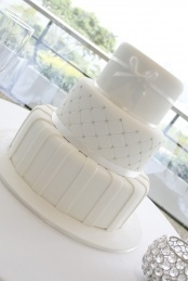 A stunning three tier white wedding cake with white stripes, diamond embossing with swarovski crystals and a neat little bow on the top tier. www.classiccakes.com.au