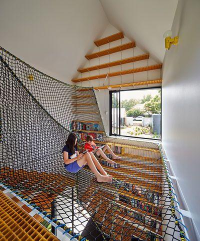 Jedna ze stěn vysokého domu je celá zakrytý poličkami na knihy. Ve vyvýšené úrovni je upevněná síť určená k relaxaci dětí.