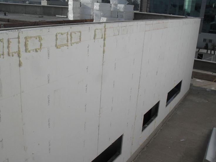 Fachada terminada de panel de estireno alta densidad y junteo con espuma de poliureteano. Ariba en la azotea estan ya los bloques de estireno para los rellenos que sustituyen a los tradicionales de piedra. Hospital con clasificacion leed.