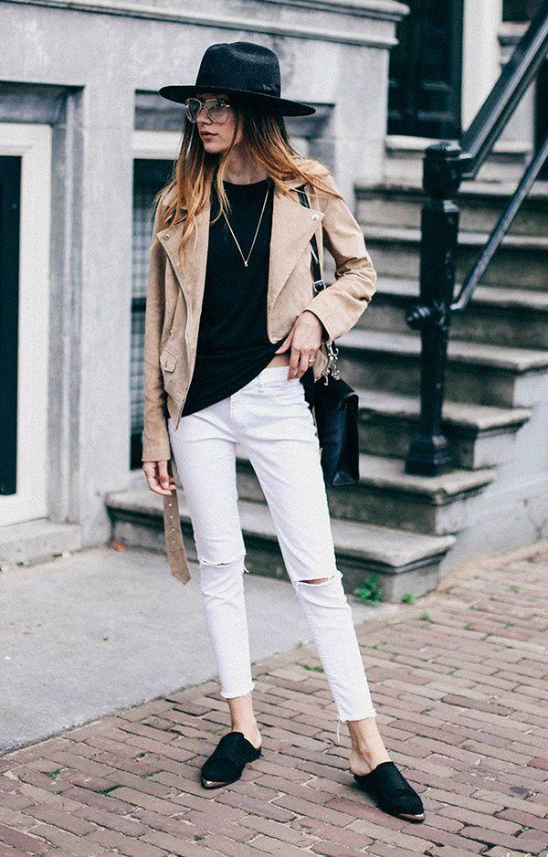 Street style look com blusa preta, casaco bege e calça jeans.