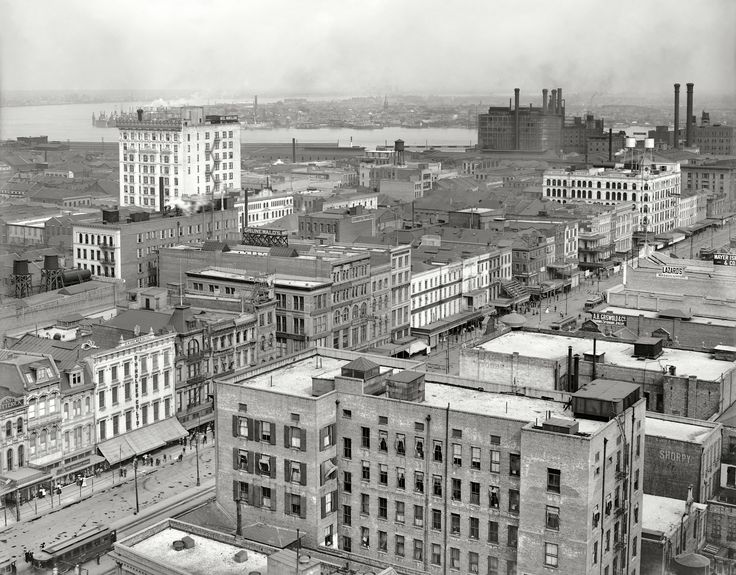 """Circa 1910. """"New Orleans and the Mississippi River from Grunewald."""" A bird's eye view of Canal Street from the Grunewald Hotel. Merchants here include Godchaux's music store as well as the big Godchaux's department store farther down the street, D.H. Holmes Co., B. Cohn Dry Goods, Marks Isaacs Co. and a One-Cent Vaudeville theater. Shorpy Historical Photo Archive :: Old New Orleans: 1910"""
