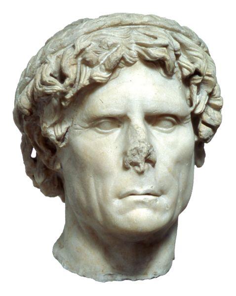 Μαρμάρινη εικονιστική κεφαλή ιερέα, από την Αθήνα 50-25 π.Χ.  Εικονιστική κεφαλή ιερέα, από πεντελικό μάρμαρο. Βρέθηκε στην Αθήνα. Ο εικονιζόμενος άνδρας έχει πλούσια ανακατεμένα μαλλιά και φορεί δάφνινο στεφάνι, που τον χαρακτηρίζει ως ιερέα. Τα ατομικά χαρακτηριστικά αποδίδονται με έντονο ρεαλισμό. Ύψος 0,31 μ.