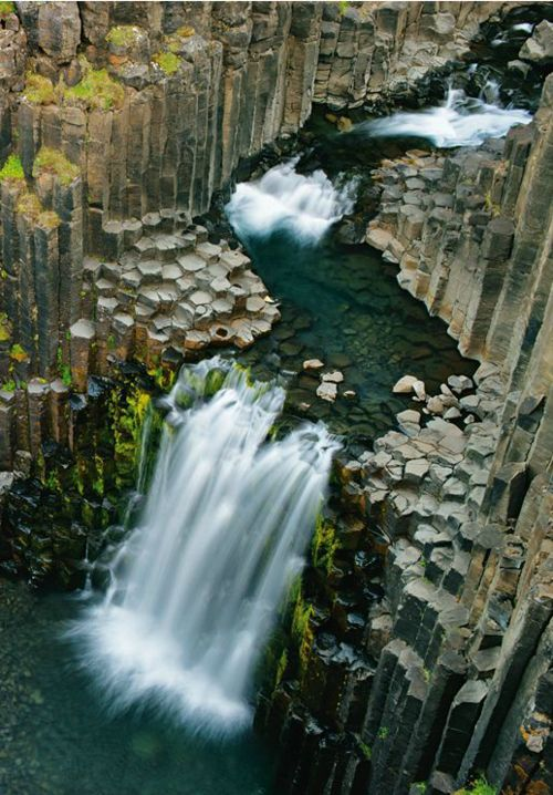 Waterfall flowing through columns formed by ancient lava flow - Iceland
