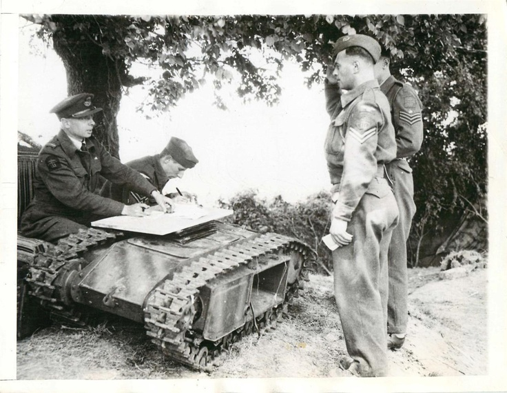 "1944- Using a knocked-out German ""Beetle"" tanks as a desk, members of an R.A.F. beach squadron receive their first pay since their arrival in Normandy."
